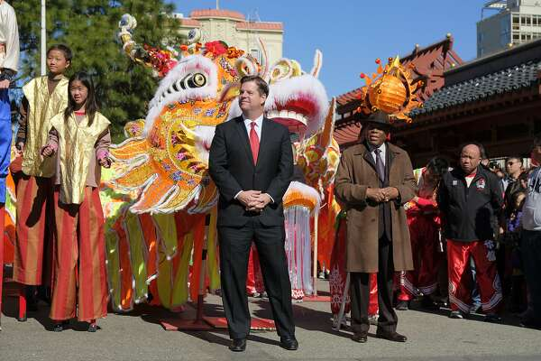 San Francisco Mayor Mark Farrell listens during a Chinese New Year celebration Friday, Feb. 16, 2018, in San Francisco. The Year of the Dog begins Friday as the Year of the Rooster comes to an end. At right is former Mayor Willie Brown. (AP Photo/Eric Risberg)