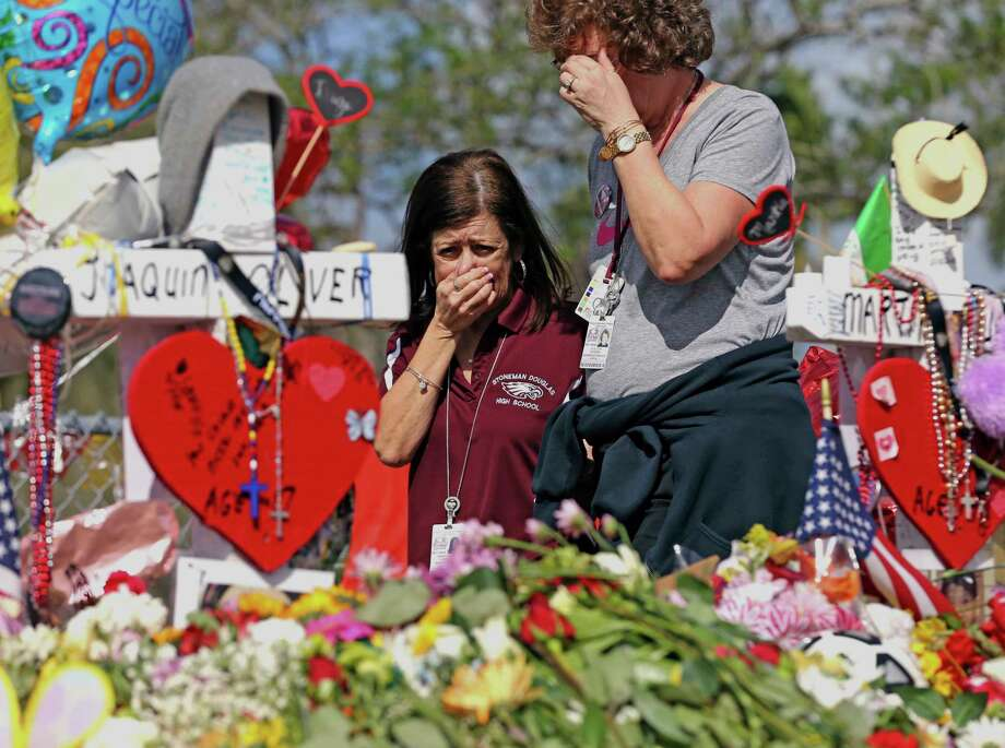 Marjory Stoneman Douglas High School administrative employees grieve after last week's deadly shooting at the school in Parkland, Fla. In Texas, Gov. Greg Abbott has called for a review of school safety procedures in the wake of the Parkland massacre. Photo: Charles Trainor Jr, MBO / Miami Herald