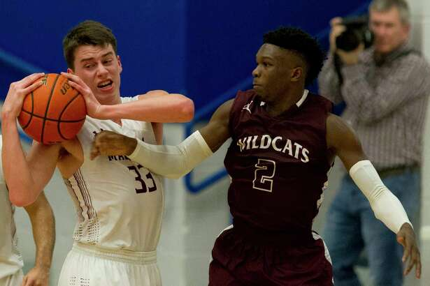 Magnolia shooting guard Jackson Moffatt (33) hauls in a rebound against Whitehouse guard Javier Neal (2) during the third quarter of a Region III-5A high school area playoff game at Crockett High School, Friday, Feb. 23, 2018, in Crockett.