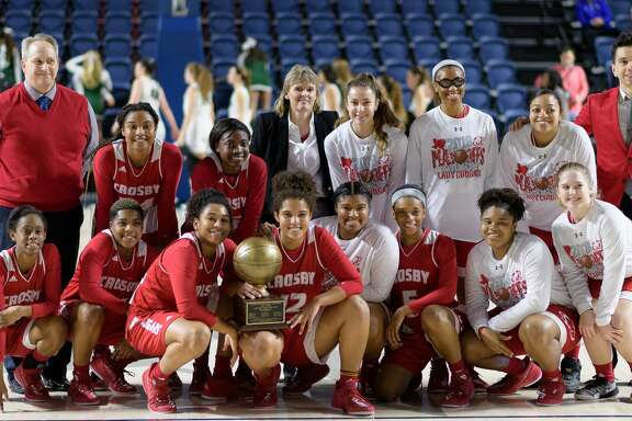 The Crosby Cougars girl's basketball team pose for a photo with their trophy after defeating the Cedar Park Timberwolves in a girls Region III 5A Semi-Final Championship basketball game on Friday, February 23, 2018 at Delmar Field House in Houston Texas.