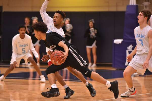 Steele's D'Angelo Griggs drives past Johnson's Tyrese Rodgers during their 6A game Friday evening at Taylor Field House.