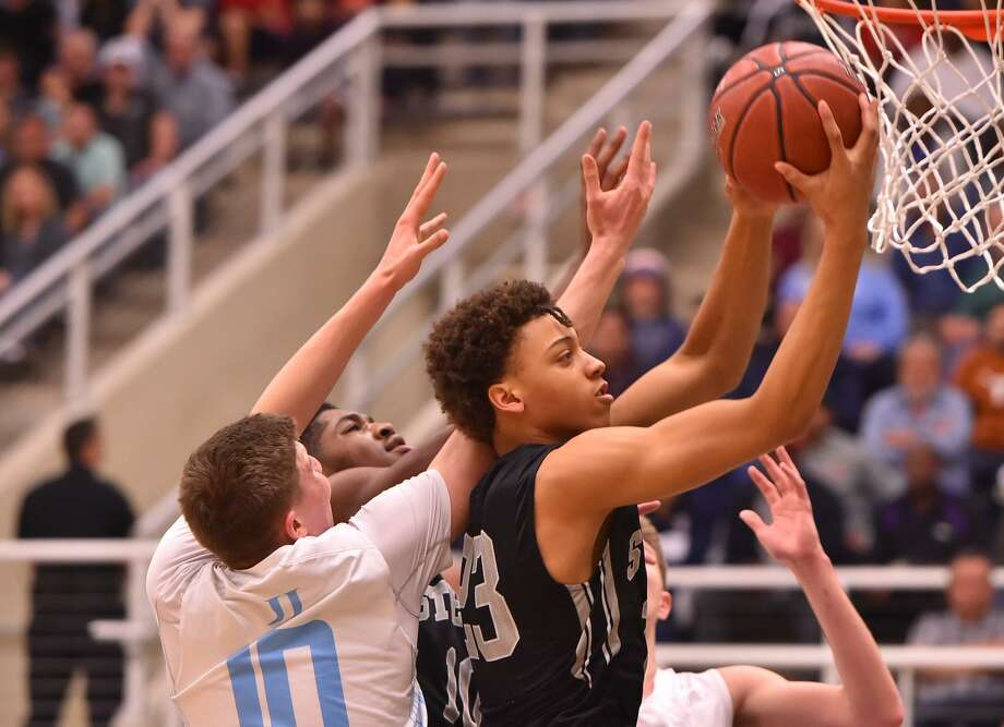 Steele's Alijah Comithier goes to the basket past Johnson's Jakob Wrenn during their 6A game Friday evening at Taylor Field House. Photo: Robin Jerstad, Freelance / ROBERT JERSTAD