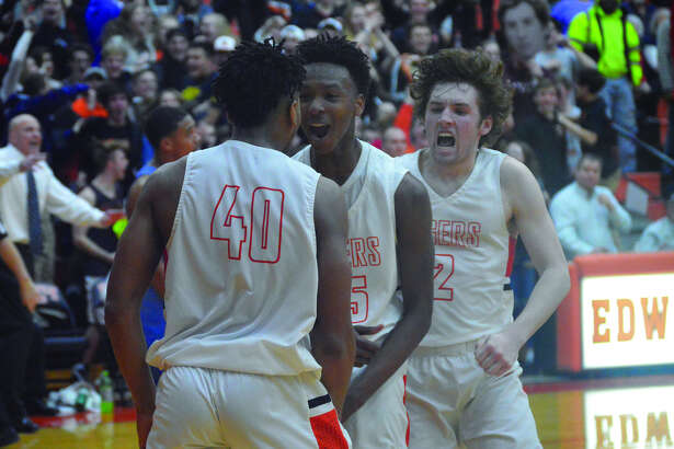 Edwardsville's R.J. Wilson (No. 40) celebrates with teammates Jaylon Tuggle, center, and Jack Marinko after scoring the go-ahead basket against Belleville East.