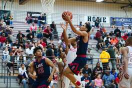 Clear Lake's Ajare Sanni (14) lays up a shot against North Shore in the area playoffs Friday, Feb. 23 at Pearland High School.