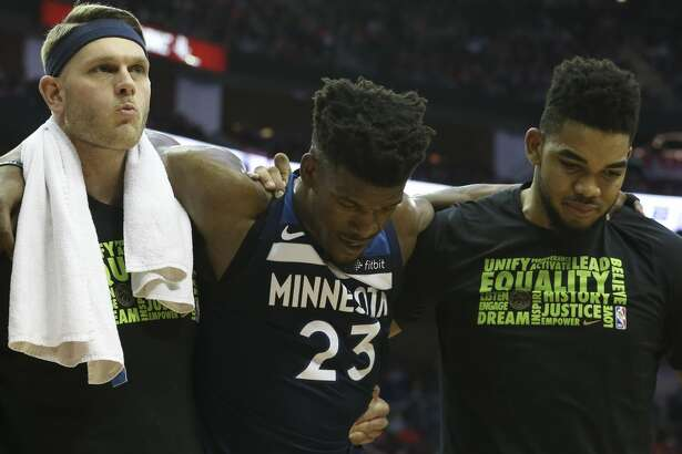 Minnesota Timberwolves guard Jimmy Butler (23) is carried off the court by teammates after appearing in pain with his knee during the third quarter of the NBA game against the Houston Rockets at Toyota Center on Friday, Feb. 23, 2018, in Houston. The Houston Rockets defeated the Minnesota Timberwolves 120-102. ( Yi-Chin Lee / Houston Chronicle )