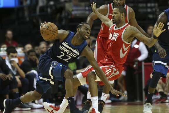 Minnesota Timberwolves forward Andrew Wiggins (22) slips after Houston Rockets forward Trevor Ariza (1) fouled on him during the second quarter of the NBA game at Toyota Center on Friday, Feb. 23, 2018, in Houston. ( Yi-Chin Lee / Houston Chronicle )