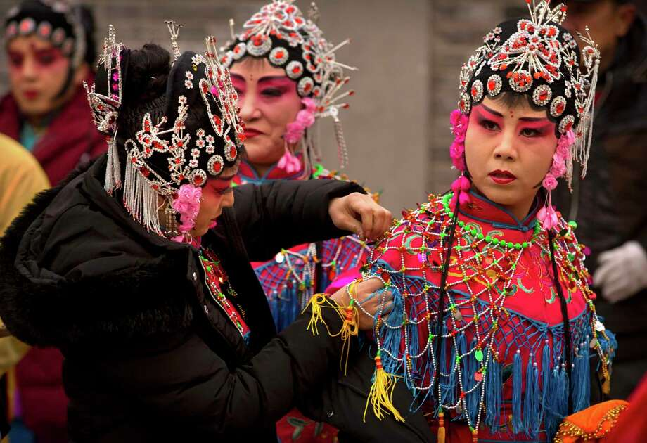 Participants adjust their costumes before their performance during a temple fair to celebrate the Lunar New Year holiday at a public park in Beijing. Chinese around the world celebrated the arrival of the Year of the Dog on Friday, Feb. 16 with family reunions, firecrackers and traditional food. (AP Photo/Mark Schiefelbein, File) Photo: Mark Schiefelbein, STF / Copyright 2018 The Associated Press. All rights reserved.