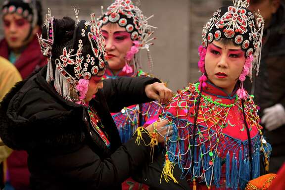 Participants adjust their costumes before their performance during a temple fair to celebrate the Lunar New Year holiday at a public park in Beijing. Chinese around the world celebrated the arrival of the Year of the Dog on Friday, Feb. 16 with family reunions, firecrackers and traditional food. (AP Photo/Mark Schiefelbein, File)