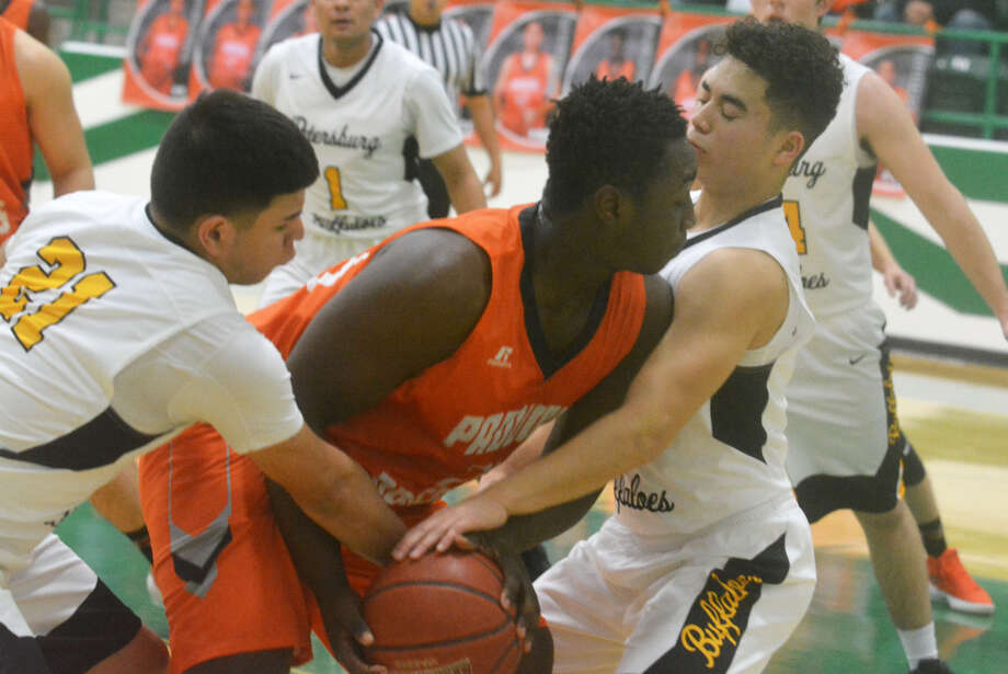 Petersburg's Yovahn Marroquin, left, and Tristan Garza, right, try to tie up Paducah's Keyvondra Richardson during a UIL Class 1A area round playoff game at Floydada Friday night. Photo: Skip Leon/Plainview Herald