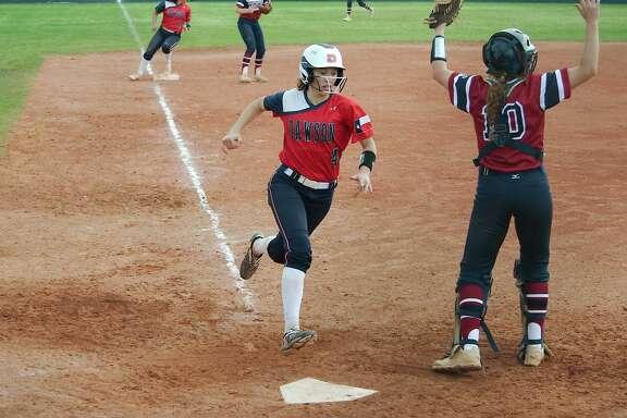 Dawson's Isabella Richey (4) crosses home plate to score a run against Tompkins Friday, Feb. 23 at Dawson High School.