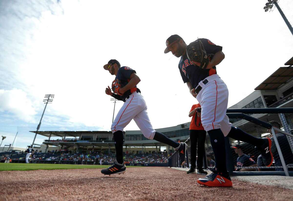 Houston Astros shortstop Carlos Correa (1) and second baseman Jose Altuve (27) run out of the dugout to start of the Astros Braves spring training game at The Fitteam Ballpark of the Palm Beaches, Saturday, Feb. 24, 2018, in West Palm Beach.