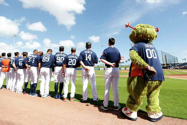Orbit and the Houston Astros line up for the National Anthem before the start of the Astros Braves spring training game at The Fitteam Ballpark of the Palm Beaches, Saturday, Feb. 24, 2018, in West Palm Beach.