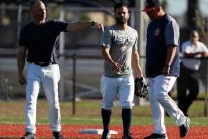 Houston Astros bench coach Joe Espada taps Jose Altuve after he and Carlos Correa finished working on early morning drills during spring training at The Fitteam Ballpark of the Palm Beaches, Saturday, Feb. 24, 2018, in West Palm Beach.