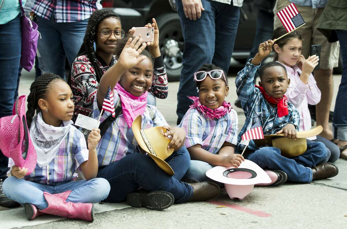 Parade goers wave as they watch the Houston Livestock Show and Rodeo Parade on Saturday, Feb. 24, 2018, in Houston. ( Brett Coomer / Houston Chronicle )