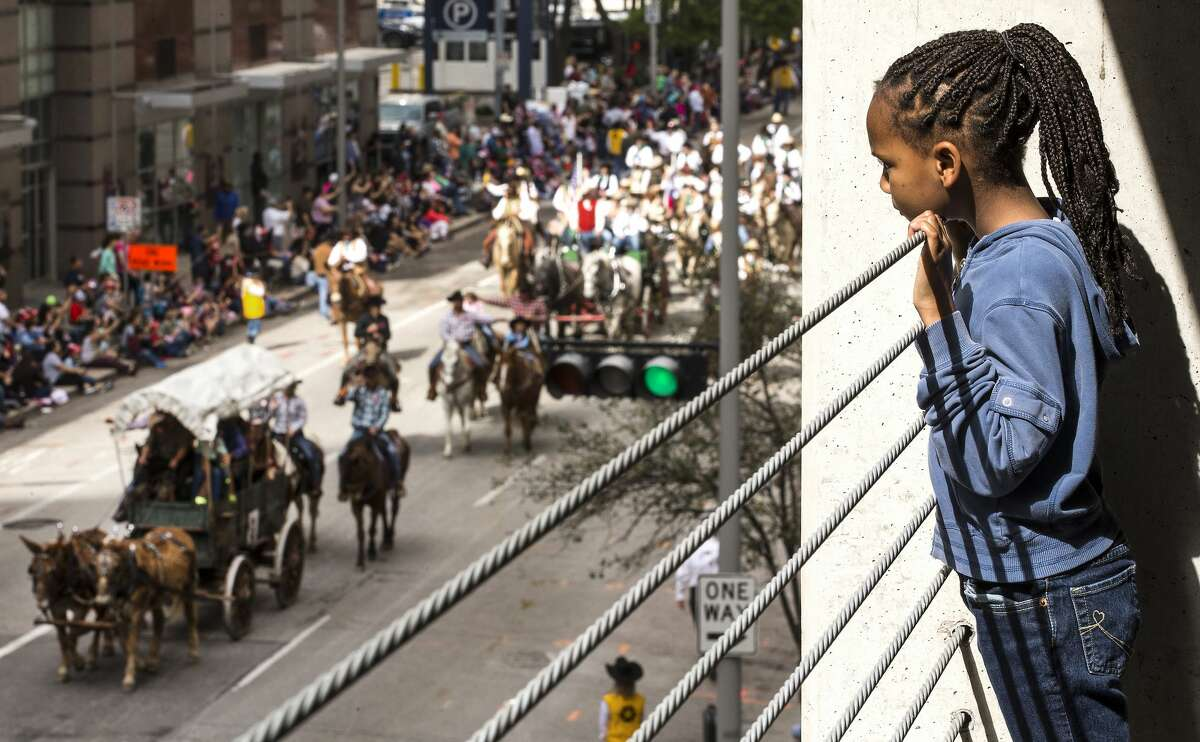 Janya Chavis, 7, takes in the Houston Livestock Show and Rodeo Parade from a parking garage on Saturday, Feb. 24, 2018, in Houston. ( Brett Coomer / Houston Chronicle )