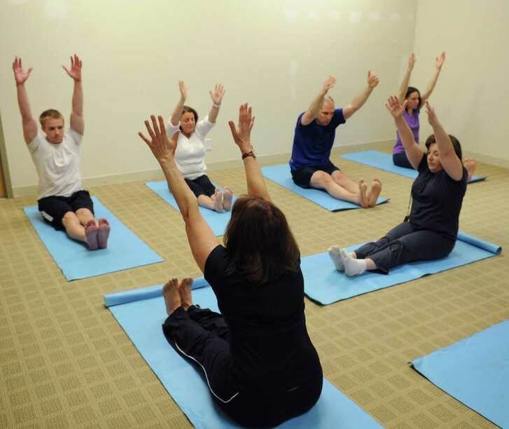 Employees do yoga during the lunch break as part of a wellness program promoted by their company.