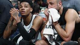 San Antonio Spurs guard Dejounte Murray, left, and guard Manu Ginobili sit on the bench late in the second half of an NBA basketball game against the Denver Nuggets on Friday, Feb. 23, 2018, in Denver. The Nuggets won 122-119. (AP Photo/David Zalubowski)