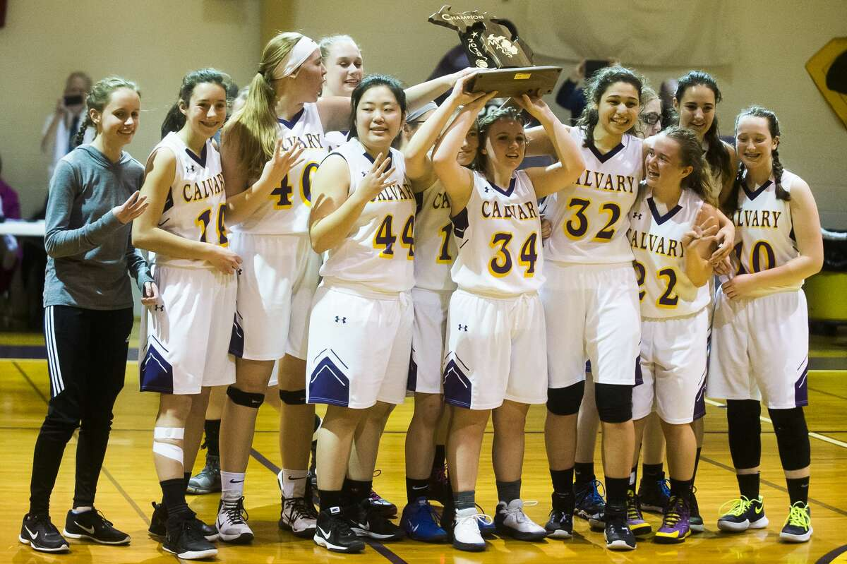 Calvary Baptist players hold their trophy after their 59-50 victory over Lake Orion Baptist in the Michigan Association of Christian Schools championship on Saturday at Springfield Christian Academy in Clarkston.