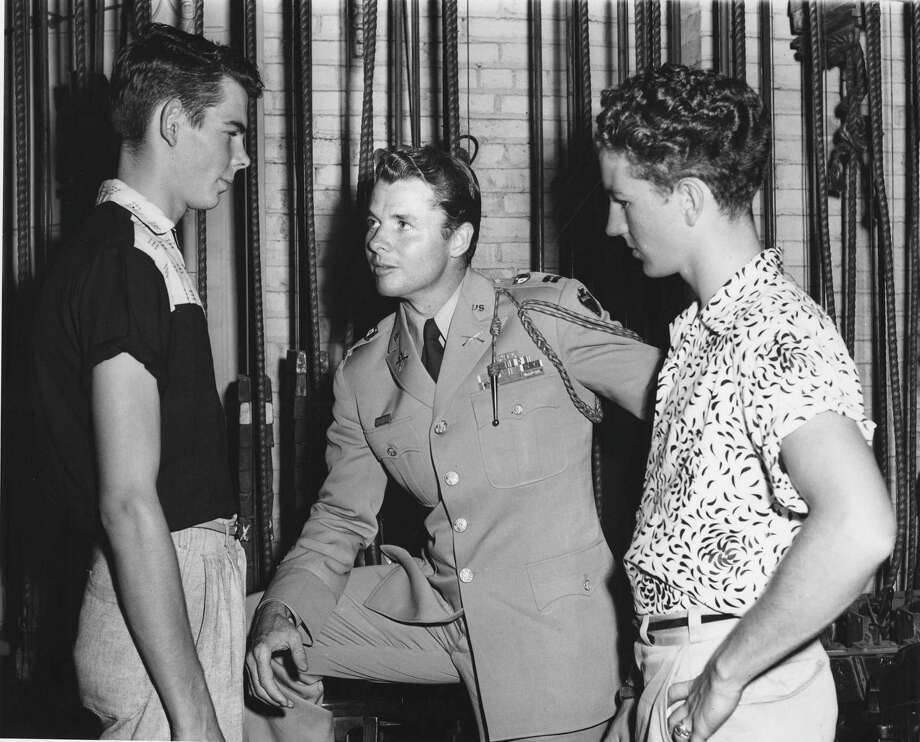 "World War II hero and movie star Audie Murphy (center) talks with two unidentified youths during his August 1955 visit to San Antonio to promote the military and his new movie, ""To Hell and Back,"" based on his autobiography. The 32 young men involved in the mock enlistment ceremony, who were ""sworn in"" by Murphy, had not yet received their uniforms. Photo: Courtesy /"