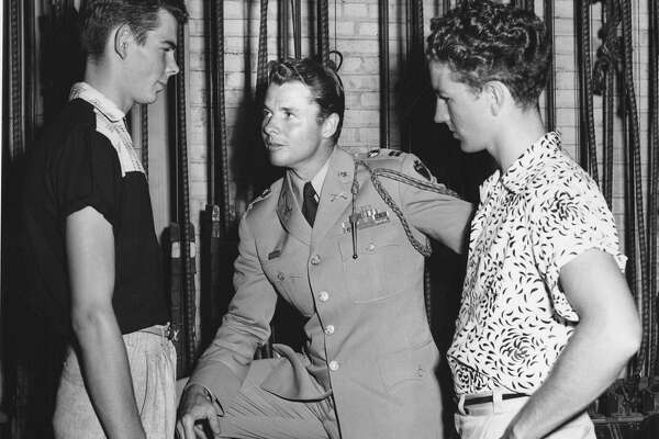 "World War II hero and movie star Audie Murphy (center) talks with two unidentified youths during his August 1955 visit to San Antonio to promote the military and his new movie, ""To Hell and Back,"" based on his autobiography. The 32 young men involved in the mock enlistment ceremony, who were ""sworn in"" by Murphy, had not yet received their uniforms."