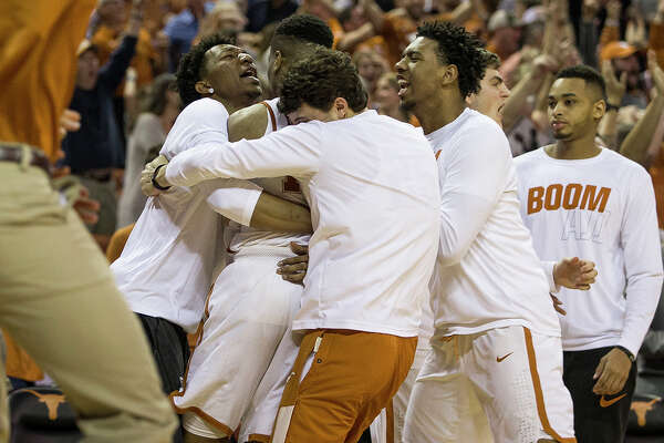Texas players celebrate with guard Kerwin Roach II (12) after Roach II made the game-winning shot to defeat Oklahoma State 65-64 in an NCAA college basketball game in Austin, Texas, on Saturday, Feb. 24, 2018. (Nick Wagner /Austin American-Statesman via AP)