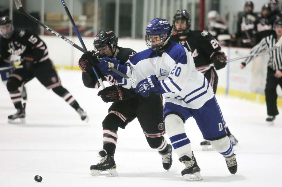 Fin Batson and Campbell Lewis chase after the puck during Darien's victory over New Canaan at the Darien Ice Rink in Darien, Conn. on Saturday, February 24, 2018. Photo: Chris Palermo / For Hearst Connecticut Media / Stamford Advocate Freelance