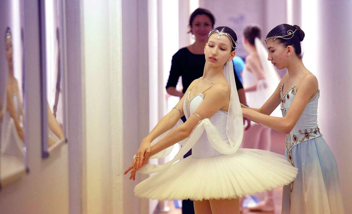 From left, Carolina Rivera is help with her costume by her twin sister Victoria Rivera as they prepare to perform solo routines during a mini-showcase of the Greenwich Ballet Academy dancers on Saturday, Feb. 24, 2018 in Port Chester, New York. The dancers are preparing for the upcoming semi-finals for the YAGP competition, an international ballet competition held in Boston and New York.