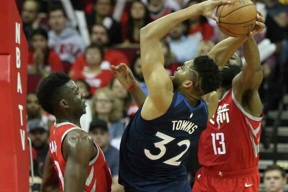 Clint Capela, left, and James Harden helped the Rockets' defense hold down Minnesota and center Karl-Anthony Towns on Friday night.