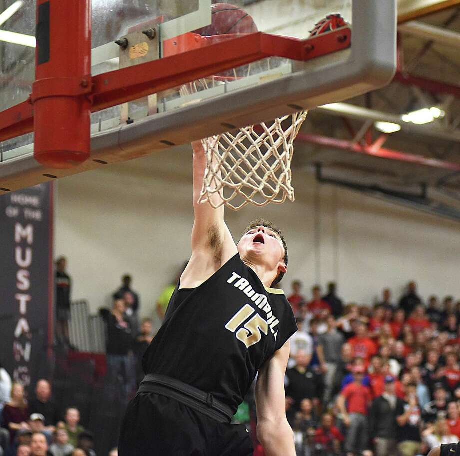 Trumbull's Chris Brown sends down a dunk to the finishing touches on Trumbull's win over Fairfield Warde in an FCIAC boys basketball quarterfinal at the Fairfield Warde gymnasium on Saturday. Photo: John Nash/Hearst Connecticut Media