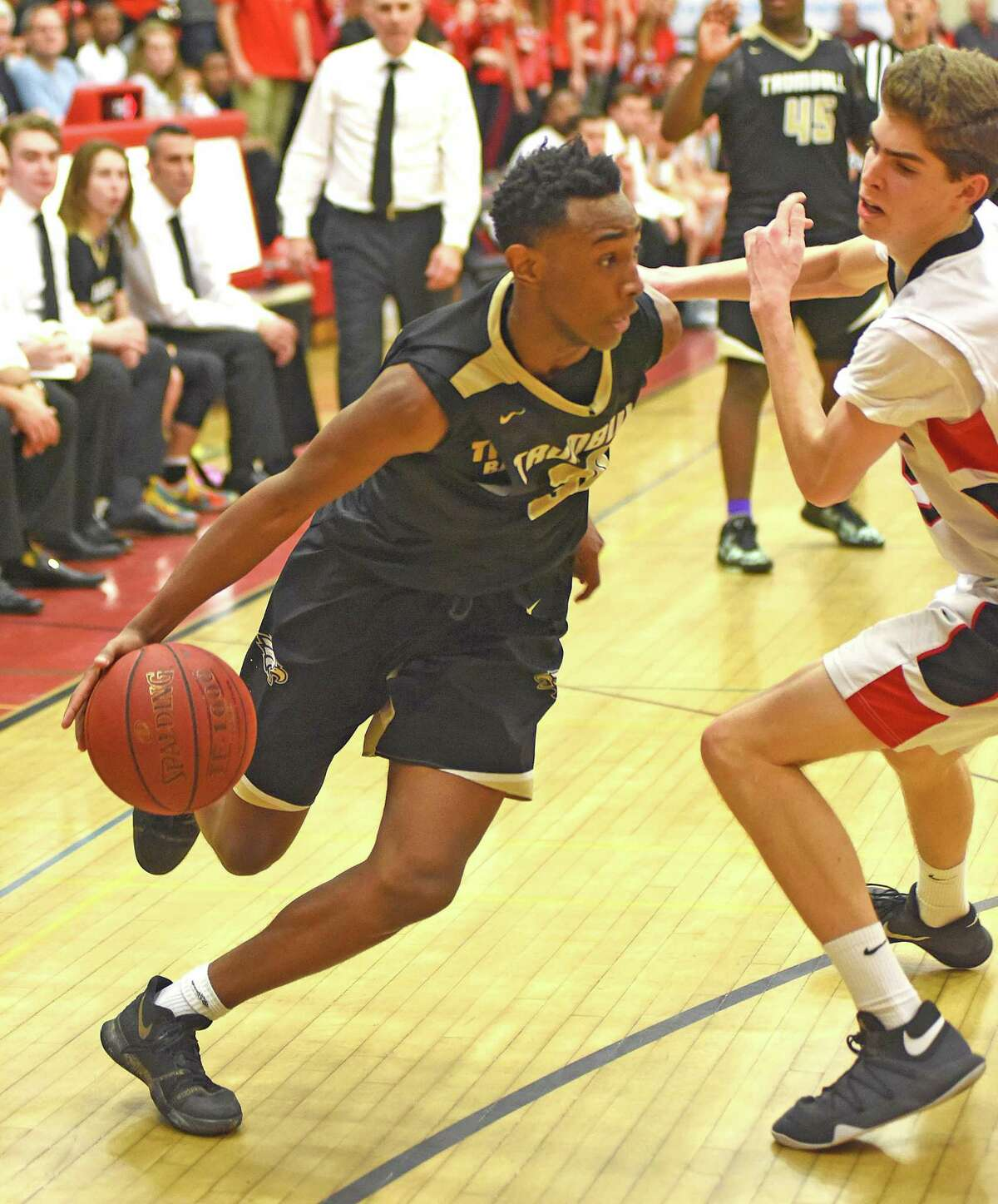Trumbull's Timmond Williams, left, drives past a Fairfield Warde defender during Saturday's FCIAC boys basketball quarterfinal at the Fairfield Warde Gymnasium. Trumbull won 65-58.
