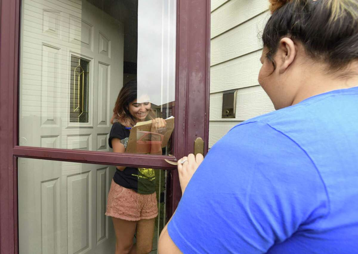 Destiny Molina, regional organizer for Congressional District 23, right, watches as Abby Arredondo commits to voting Democrat during a block walk in a West San Antonio neighborhood on Saturday, Feb. 24, 2018. Molina knocked on many doors, hoping to get potential voters to commit to voting Democrat.