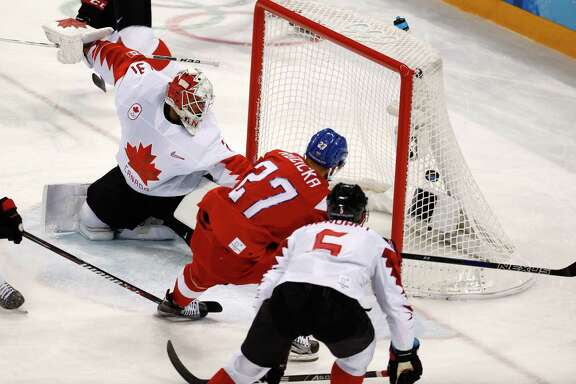 Martin Ruzicka (27), of the Czech Republic, scores a goal past goalie Kevin Poulin (31), of Canada, during the first period of the men's bronze medal hockey game at the 2018 Winter Olympics in Gangneung, South Korea, Saturday, Feb. 24, 2018.