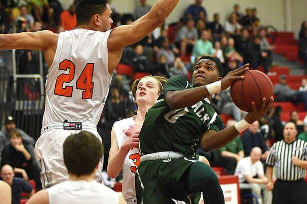 Norwalk's Tyrique Langley puts up a shot against the defense of Ridgefield's Jackson Mitchell (24) as the Tigers' Brendan McNamara, rear, and Ryan Malley (14) look on in Saturday's FCIAC quarterfinal in Fairfield on Saturday. For full results, go to thehour.com/sports.