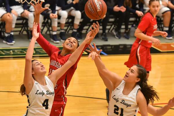 Judson's Heaven Mbaruk foghts for a rebound with Laredo Alexander's Katelyn De La Cruz (4) and Sheyla Cardenas (21) during their Region IV-6A final at Littleton Gym Satuday afternoon.