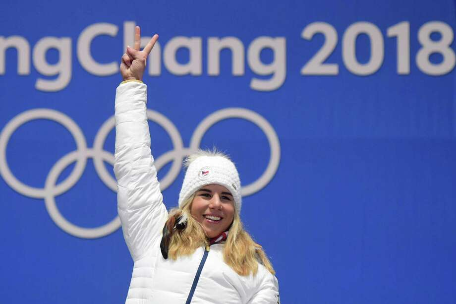 Czech Republic's Ester Ledecka celebrates on the podium after winning gold in the snowboard women's parallel giant slalom, her second gold in an unlikely combination of events. Photo: MARTIN BERNETTI, Contributor / AFP or licensors