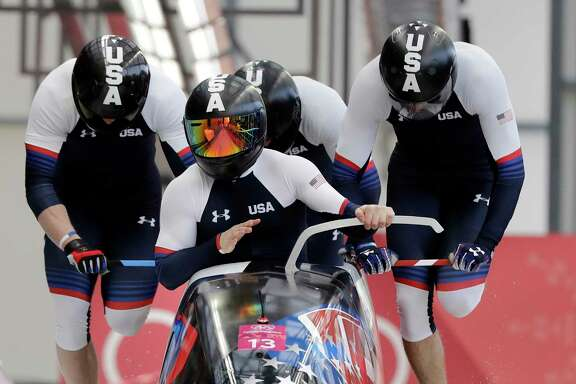 Codie Bascue, Steven Langton, Samuel McGuffie and Evan Weinstock of the U.S. start their third heat during the four-man bobsled final. The Americans went on to finish ninth.