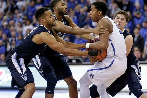 Creighton's Ty-Shon Alexander, second from right, fights with Villanova's Phil Booth, left, and Mikal Bridges for ball control.