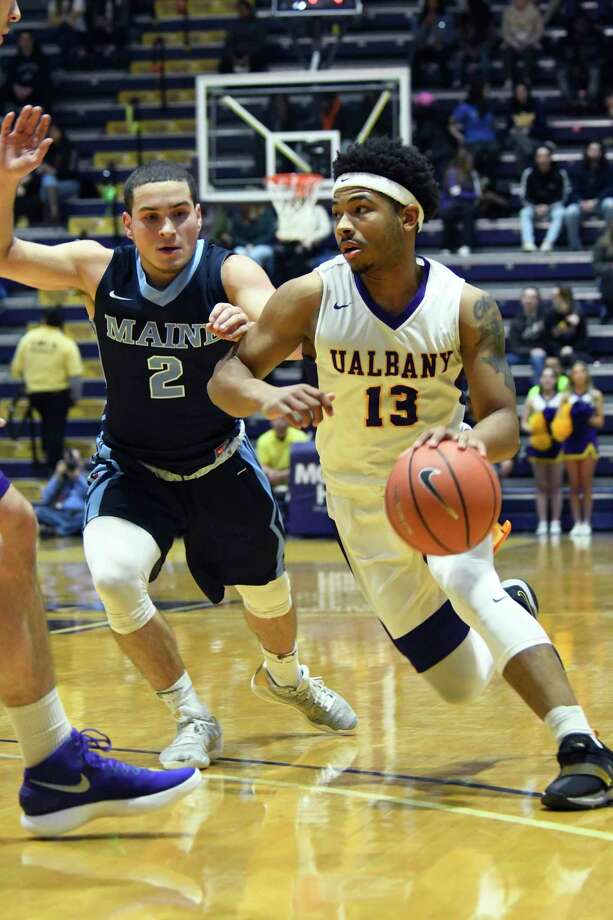UAlbany's David Nichols moves the ball toward the net as Maine's Celio Araujo follows closely during a game on Saturday, Feb. 24, 2018, at SEFCU Arena in Albany, N.Y. UAlbany finished out with a win over Maine 89-79. (Jenn March, Special to the Times Union) Photo: Jenn March / 20042388A