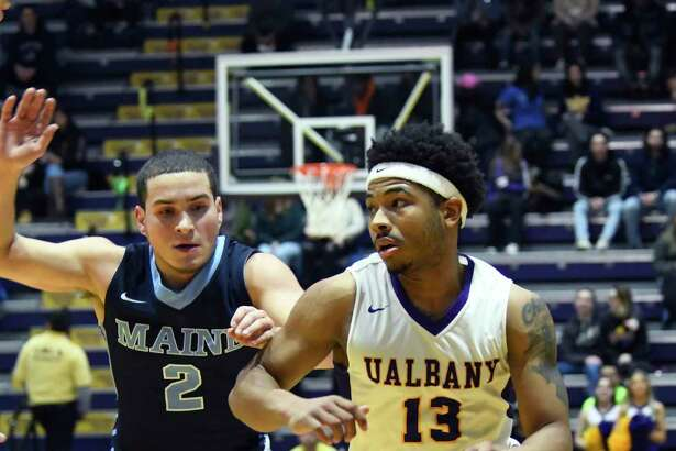 UAlbany's David Nichols moves the ball toward the net as Maine's Celio Araujo follows closely during a game on Saturday, Feb. 24, 2018, at SEFCU Arena in Albany, N.Y. UAlbany finished out with a win over Maine 89-79. (Jenn March, Special to the Times Union)