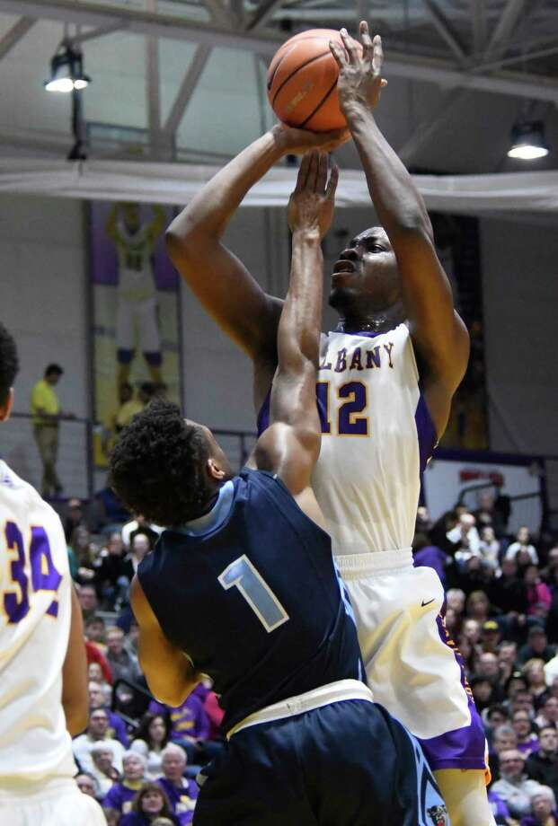 Maine's Aaron Calixte reaches to block UAlbany's Devonte Campbell as he shoots the ball during a game against Maine on Saturday, Feb. 24, 2018, at SEFCU Arena in Albany, N.Y. UAlbany finished out with a win over Maine 89-79. (Jenn March, Special to the Times Union) Photo: Jenn March / 20042388A