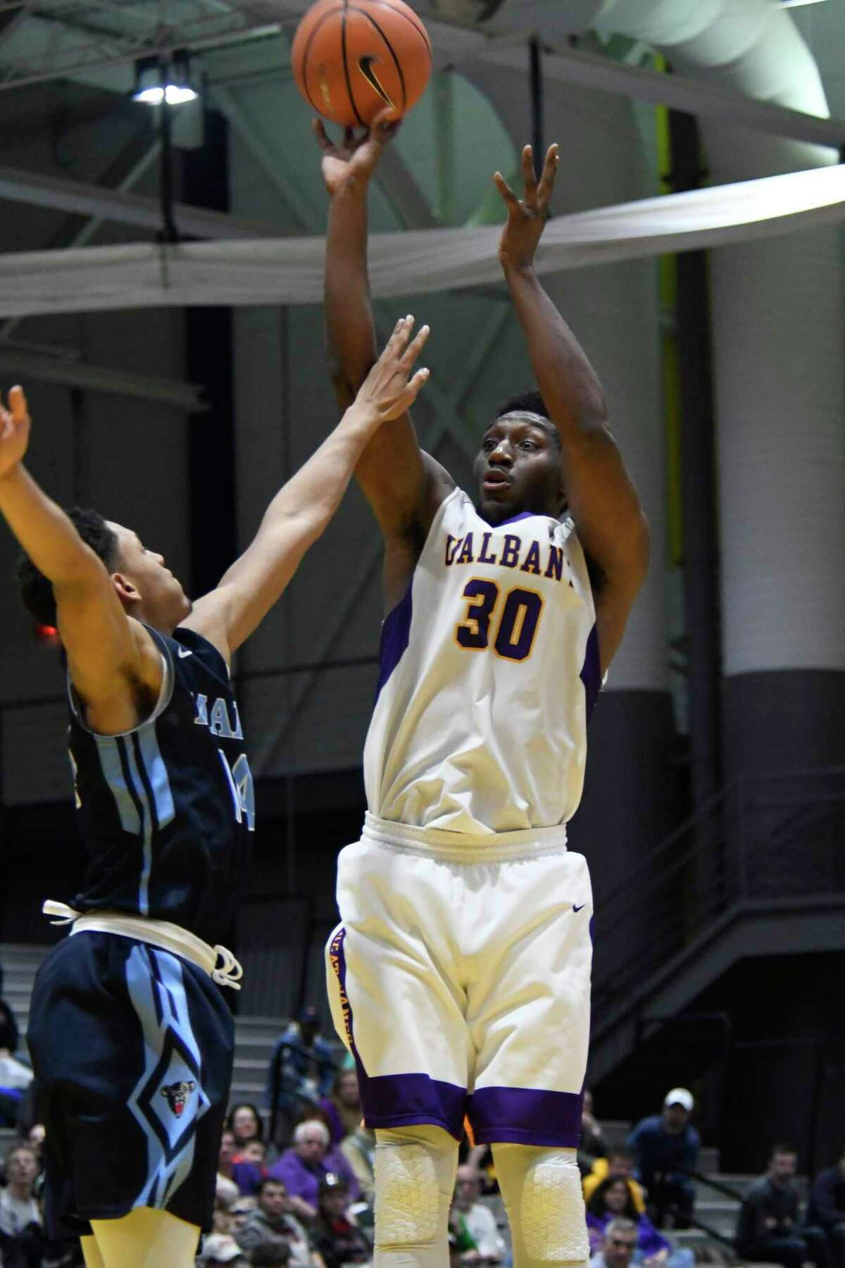 UAlbany's Travis Charles takes a shot over Maine's Isaiah White's block during a game against Maine on Saturday, Feb. 24, 2018, at SEFCU Arena in Albany, N.Y. UAlbany finished out with a win over Maine 89-79. (Jenn March, Special to the Times Union)