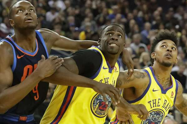 Golden State Warriors forward Draymond Green (23) and Golden State Warriors guard Nick Young (6) look to rebound from Oklahoma City Thunder forward Jerami Grant (9) on Saturday, Feb. 24, 2018 in Oakland, CA.