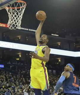 Golden State Warriors forward Kevin Durant (35) dunks over Oklahoma City Thunder forward Carmelo Anthony (7) on Saturday, Feb. 24, 2018 in Oakland, CA.
