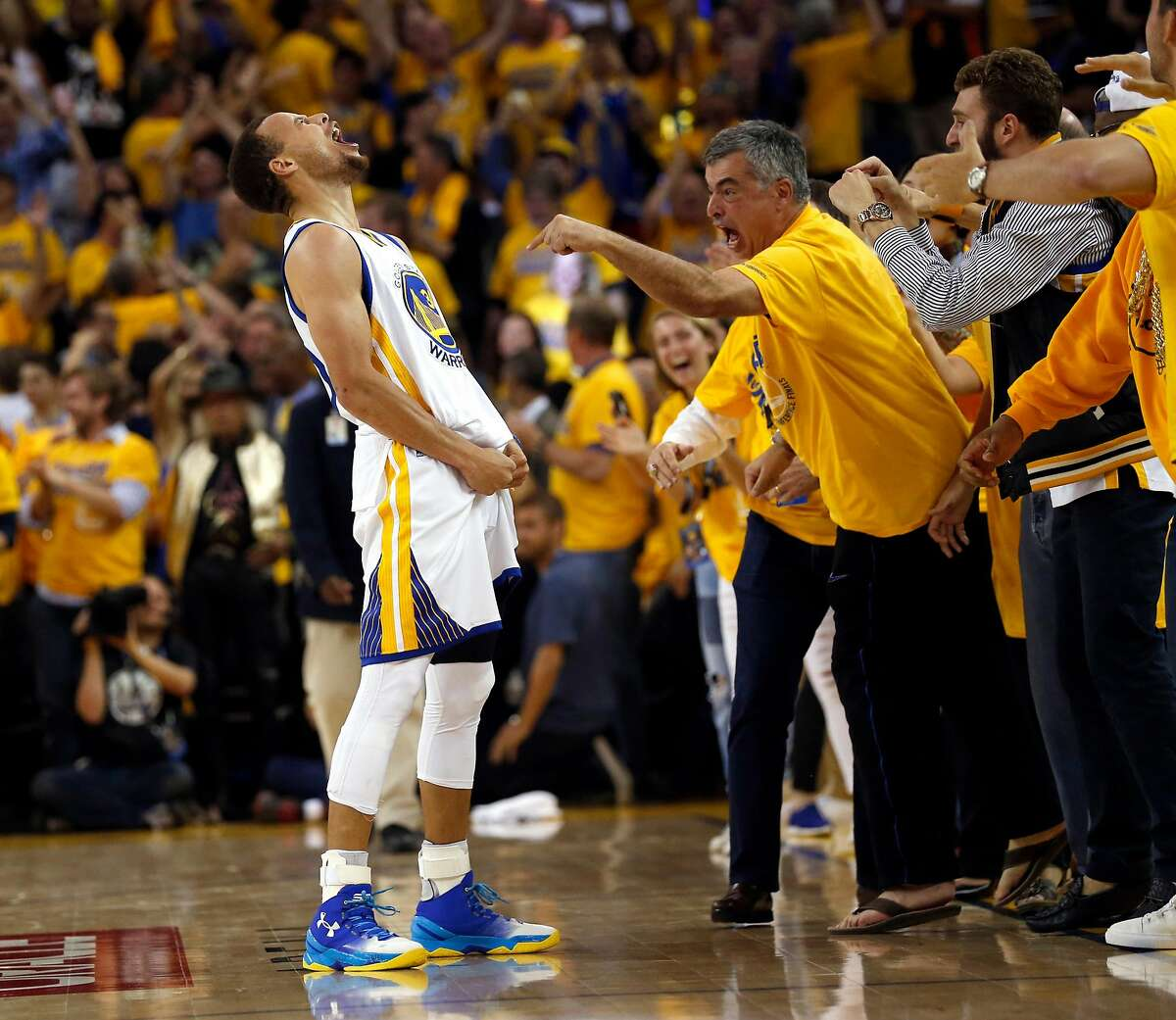 Golden State Warriors' Stephen Curry and Apple's Eddy Cue celebrates Curry's 3-pointer in final minute of 96-88 win over Oklahoma City Thunder in Game 7 of NBA Playoffs' Western Conference finals at Oracle Arena in Oakland, Calif., on Monday, May 30, 2016.