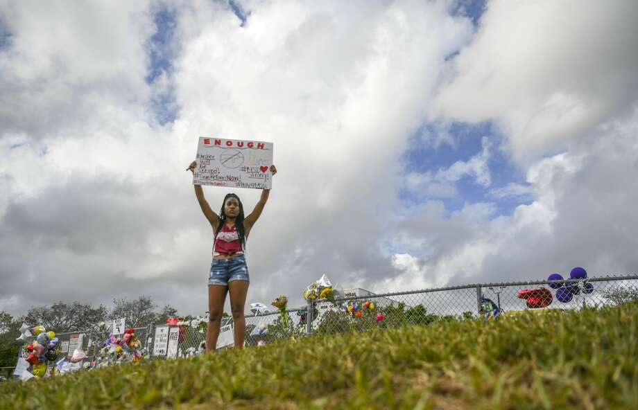 A protest of one- Douglas High senior,  Tyra Hemans, stands on a hillside outside the school where Seventeen students and teachers were killed on Wednesday at Marjory Stoneman Douglas High School in the second-deadliest shooting at a U.S. public school. Photo: The Washington Post/The Washington Post/Getty Images