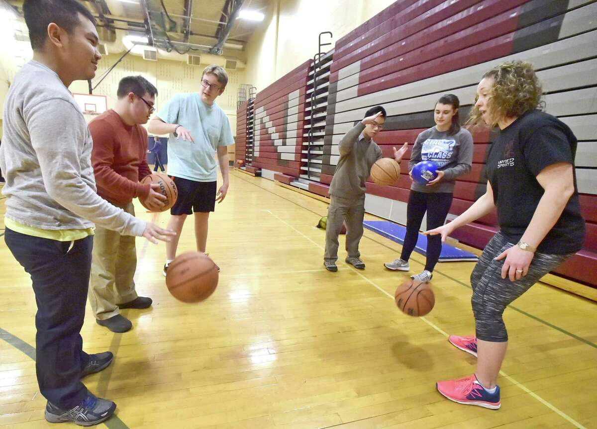 Head coach and North Haven Middle School teacher Leslie Fazzuoli, far right, demonstrates dribbling during a basketball skills review. From left are high school students Johnny Gigantone, Peter Cronin, peer Ian Crowther, Ian Cheung and peer Laura Borrelli.