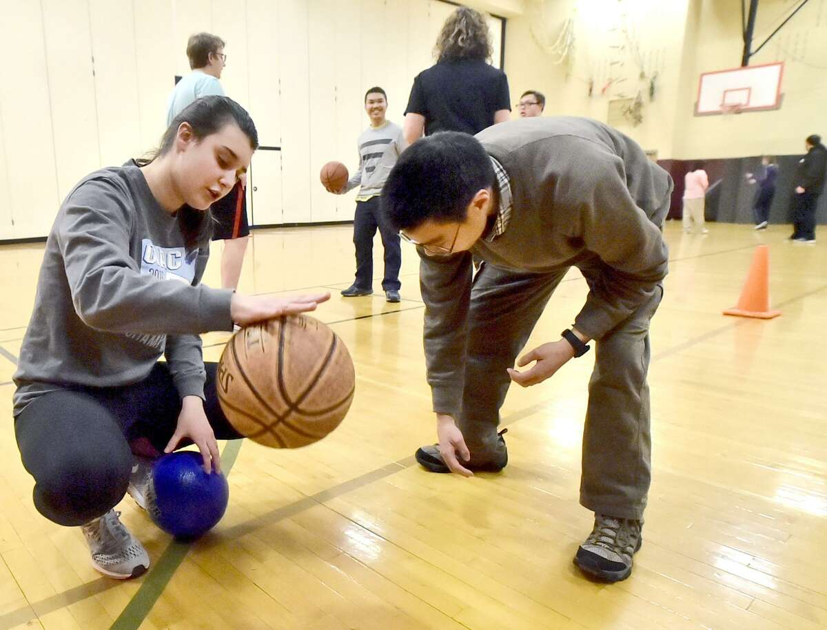 North Haven High school student and basketball teammate Laura Borrelli works on a basketball dribbling skills review with Unified Sports Special Olympics basketball athlete Ian Cheung, right, during a practice.