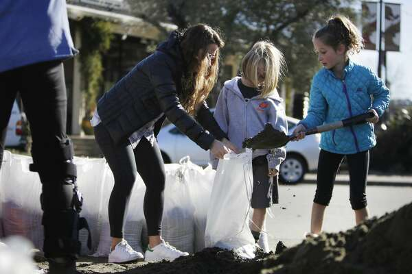 Jenny (left), Isaac and Liat Holden fill sandbags for their home along Sunny Hills Drive in San Anselmo in January 2017.