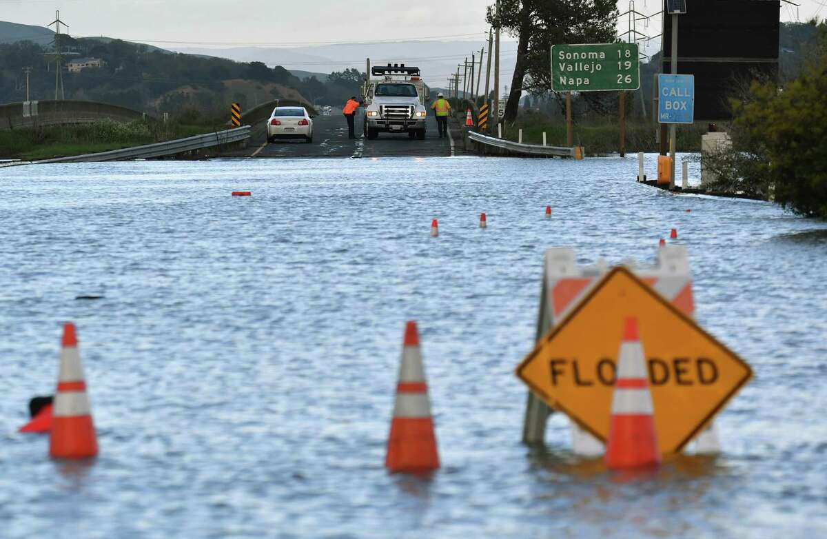 Caltrans workers prepare to drive through a flooded section of Highway 37 in Novato last February.