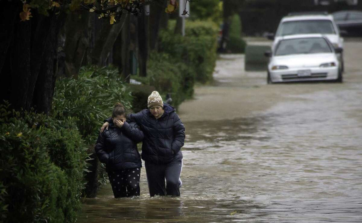 Two women brave waist-high floodwaters along Armstrong Avenue in Novato in January 2017.